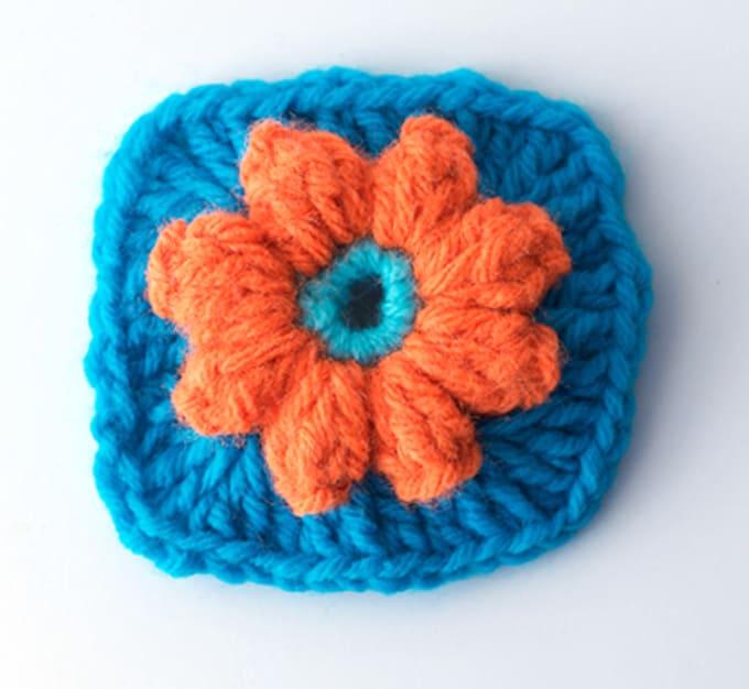 Crochet orange flower on blue granny square
