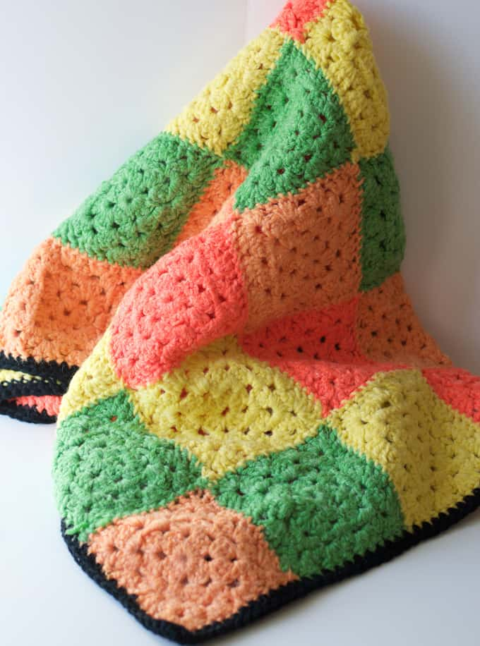 Crochet granny square afghan in yellow, green and oranges with black border