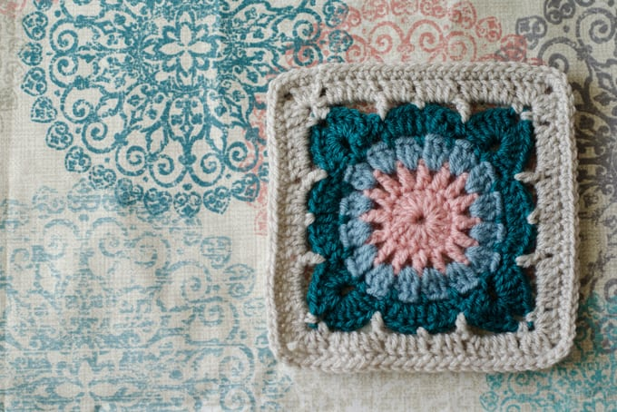 crochet afghan square on fabric in ivory, blue, pink and gray