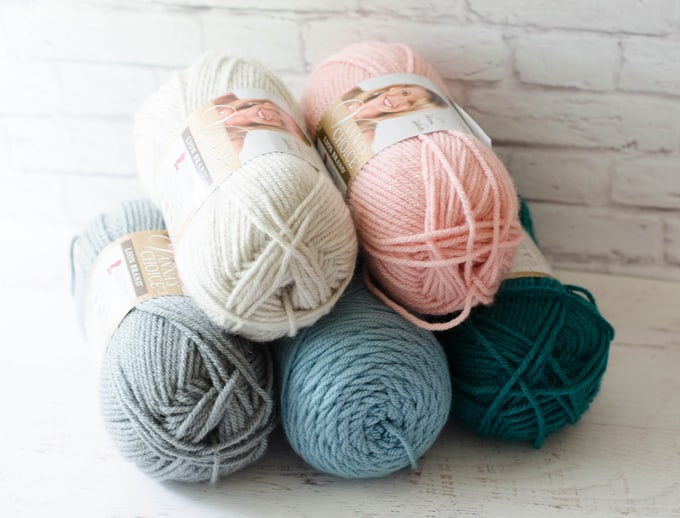 how much yarn to crochet a blanket: ivory, pink, gray, blue and teal yarn