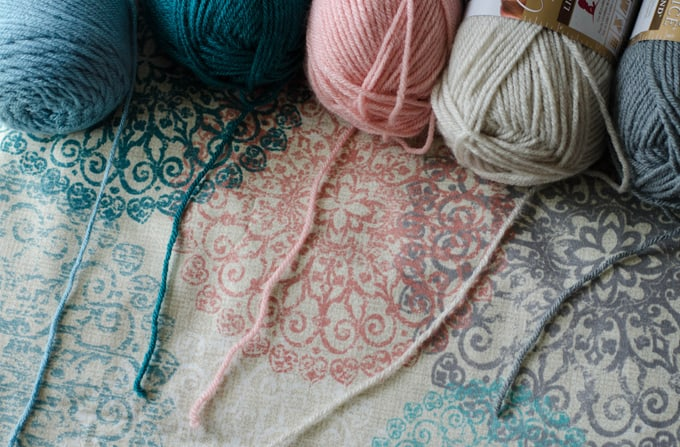 bue, teail, pink, ivory and gray yarn on multi color fabric for how much yarn to crochet a blanket