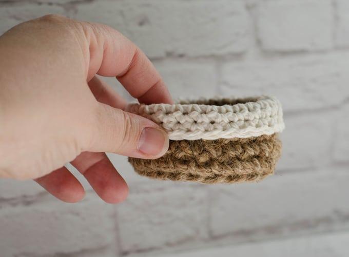 Hand holding mini jute crochet basket