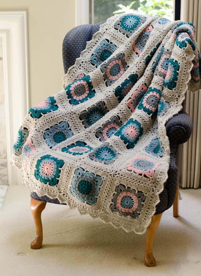 Crochet afghan in blue, teal, pink , gray and off white yarn.