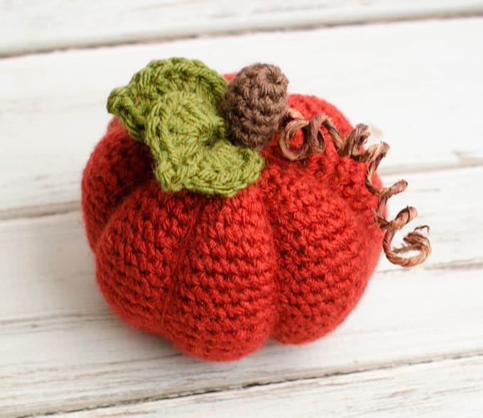 orange crochet pumpkin with green leaf, brown stem and curly tendril