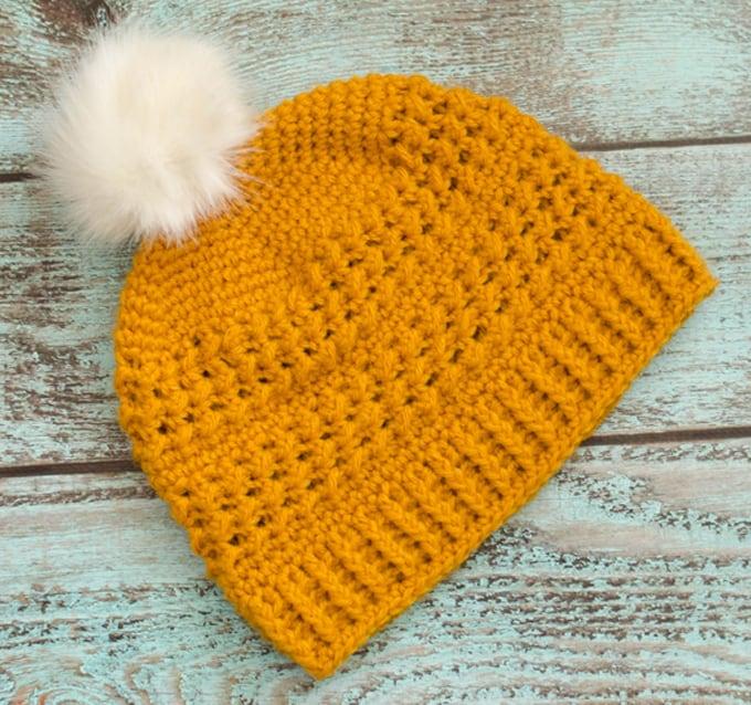 Yellow crochet hat with white fur pom pom