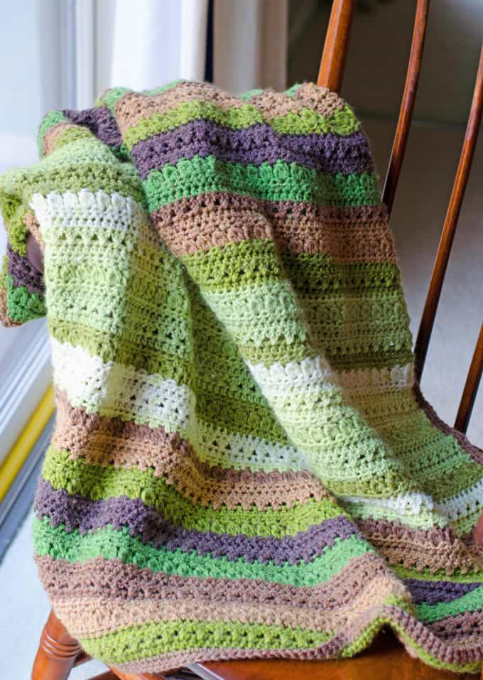Green and brown Fields and Furrows Crochet Afghan on a chair