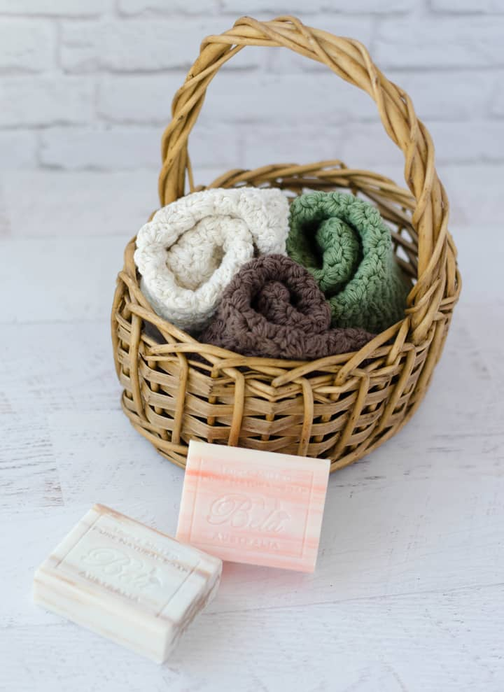 crochet dishcloths in ivory, green and brown in basket with soap