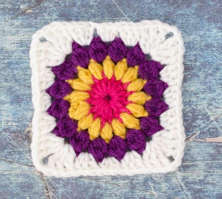 Sunburst Granny Square in pink, yellow, purple and white yarn