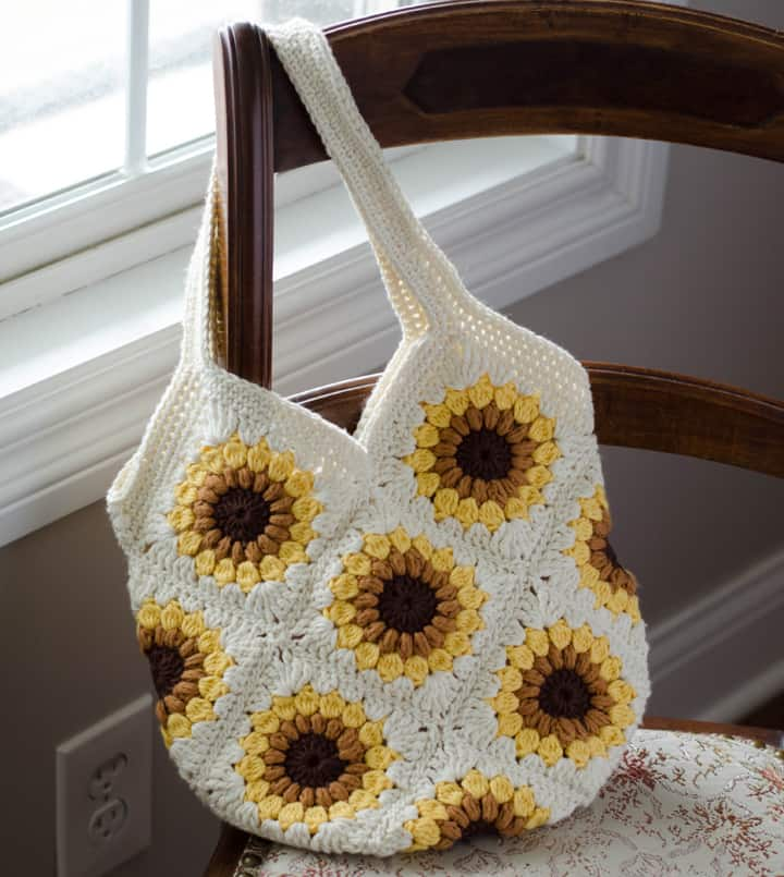 crochet granny square bag in off-white, yellow, gold and brown yarn on chair