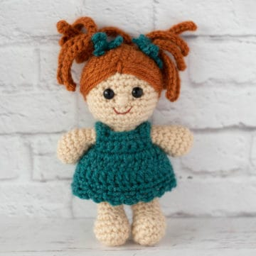 standing crochet doll with rust color hair and teal dress