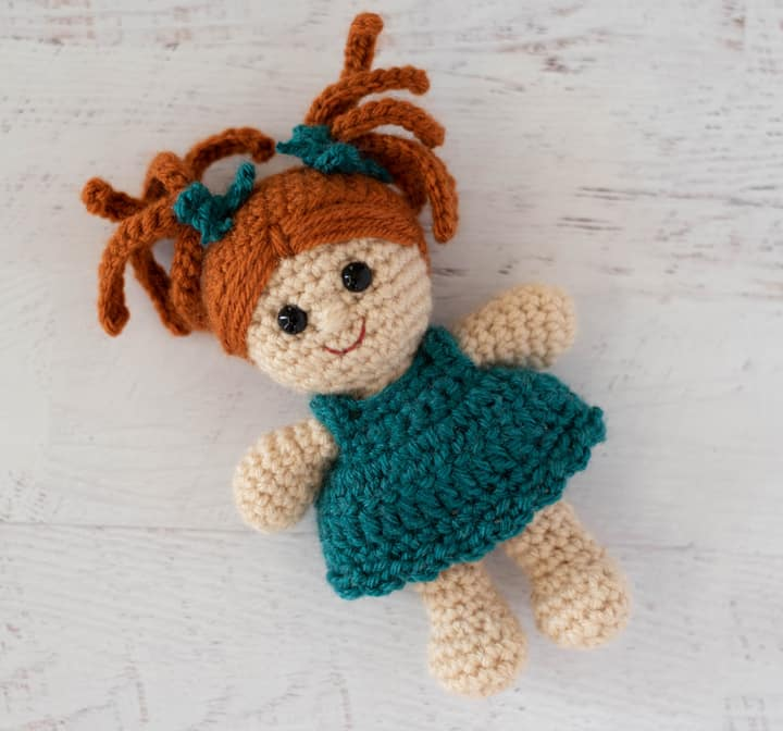 crochet doll with rust color hair and teal dress