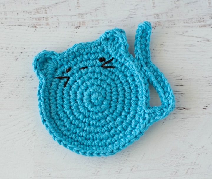 blue crochet cat coaster with embroidered features