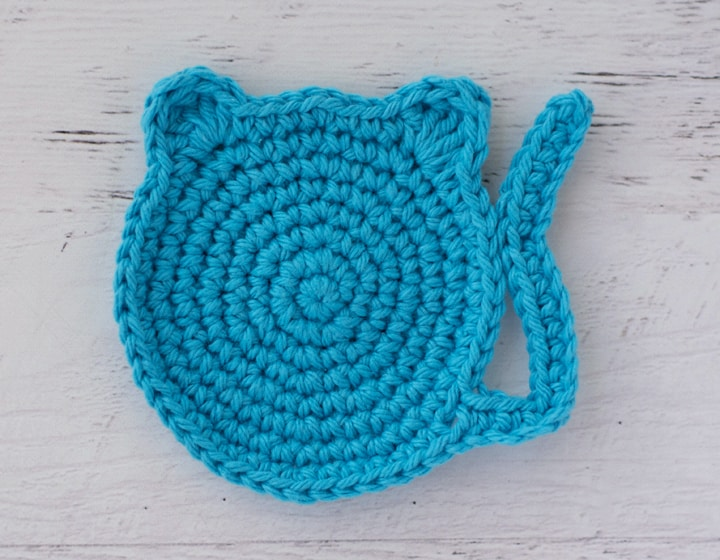 blue crochet coaster in the shape of a cat