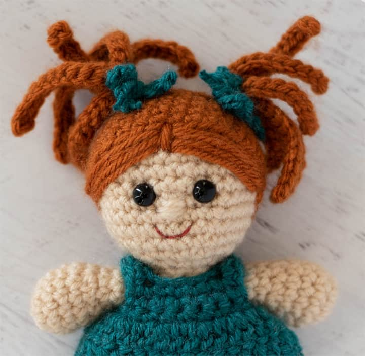 Crochet doll head with rust color hair, eyes and smile