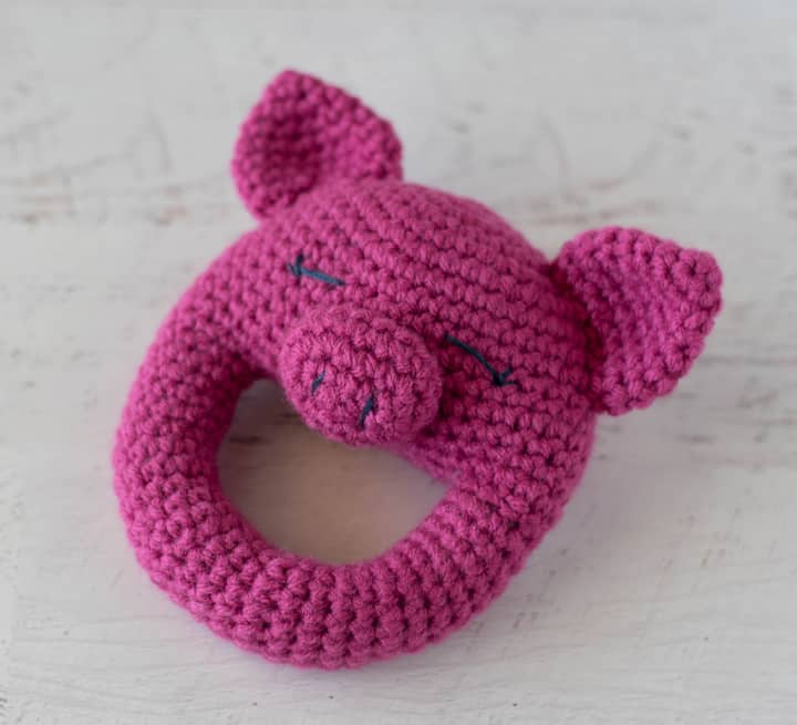 A pink crochet pig rattle on an angle