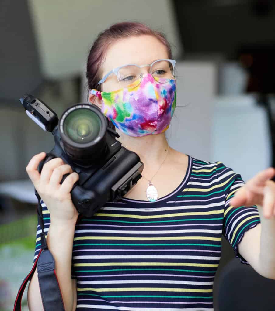 Woman with camera wearing a cloth face mask