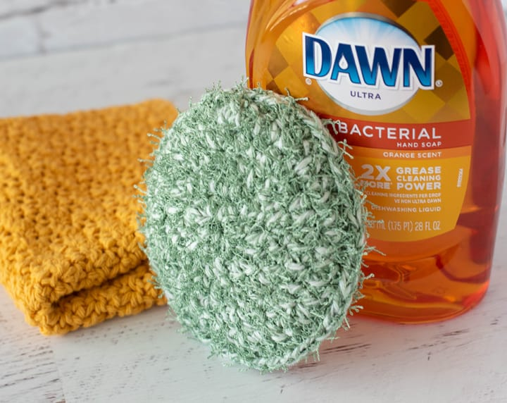 green crochet dish scrubber, yellow dishcloth and dish soap