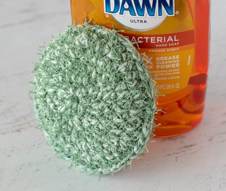 green crochet dish scrubber with dish soap