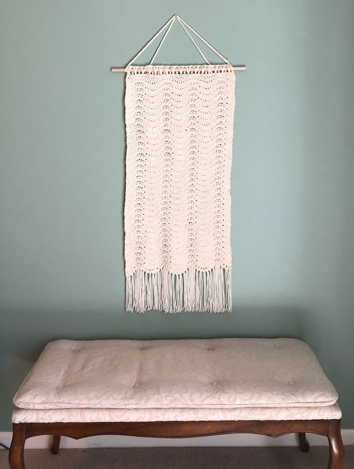 crochet wall hanging over bench