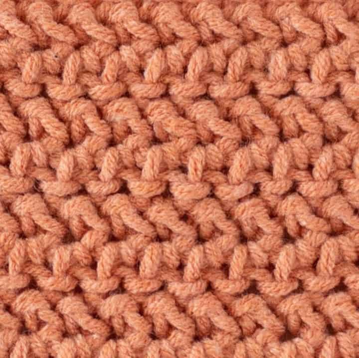 close up view of herringbone half double crochet stitch in salmon color yarn