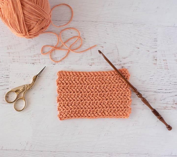 Herringbone half double crochet stitch swatch with yarn, hook and scissors