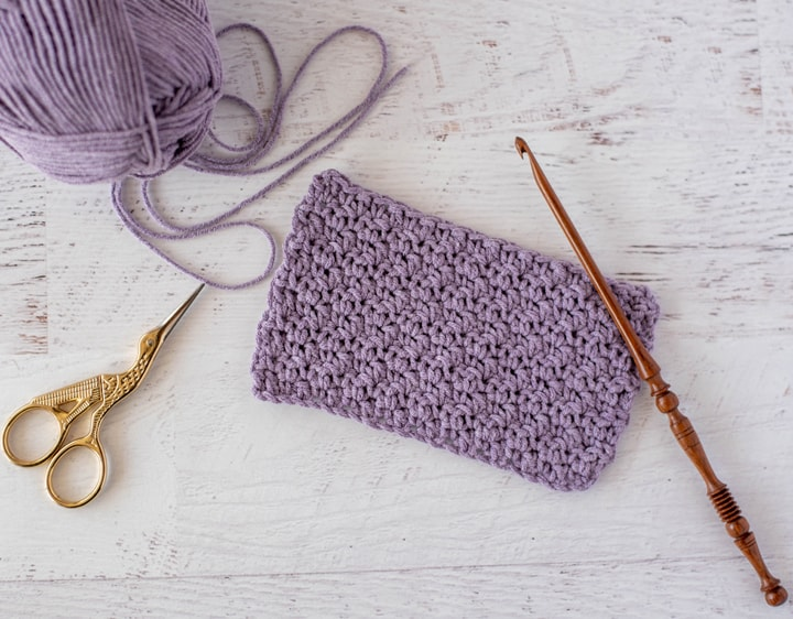 Purple crochet swatch sample of moss stitch with wooden hook and scissors