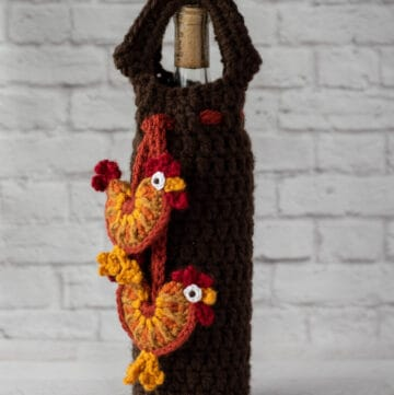 crochet rooster appliques hanging from brown wine bottle cover with bottle of wine