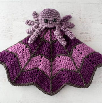 crochet spider on a light and dark purple crochet lovey blanket