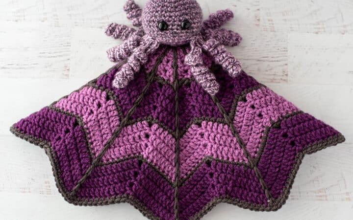 crochet spider on a light and dark purple crochet lovey blanket