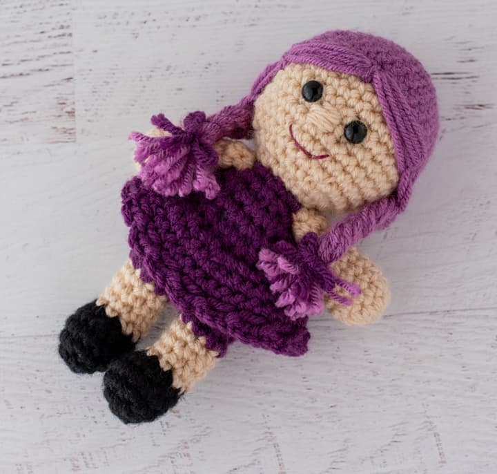 crochet doll with purple dress and pink hair