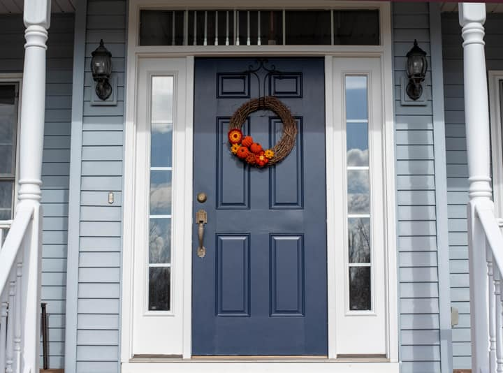 Grapevine wreath with crochet pumpkins and flowers on a blue door on a porch