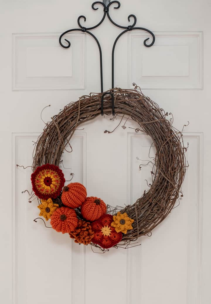 Grapevine wreath with crochet pumpkins and flowers on a white door