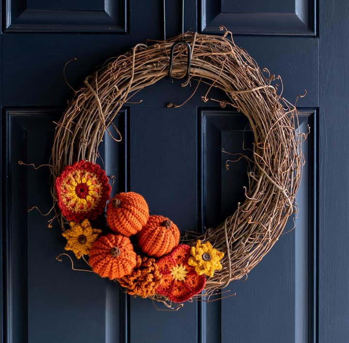 Grapevine wreath with crochet pumpkins and flowers on a blue door