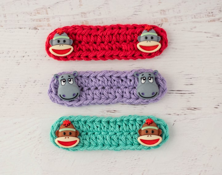 Red, Purple and Green crochet ear savers with monkey and hippo buttons