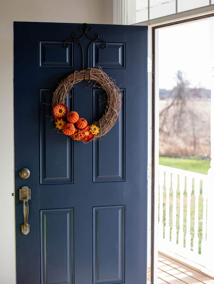 Grapevine wreath with crochet pumpkins and flowers on a blue door overlooking a porch and yard