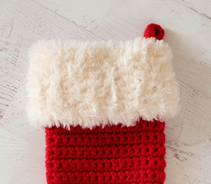 red crochet christmas stocking with white fur trim
