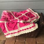 crochet afghan with pink heart squares and a white lacy like border in a basket on a porch