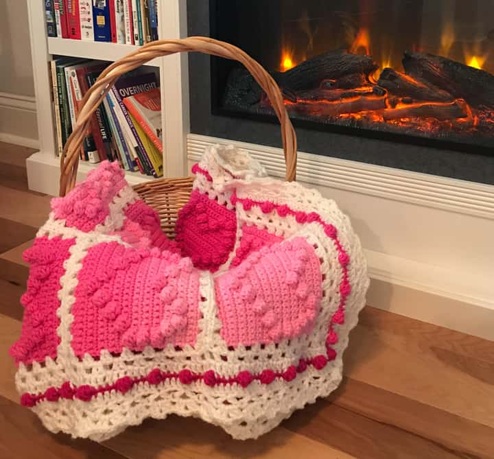 crochet afghan with pink heart squares and a white lacy like border by a fireplace and bookcase