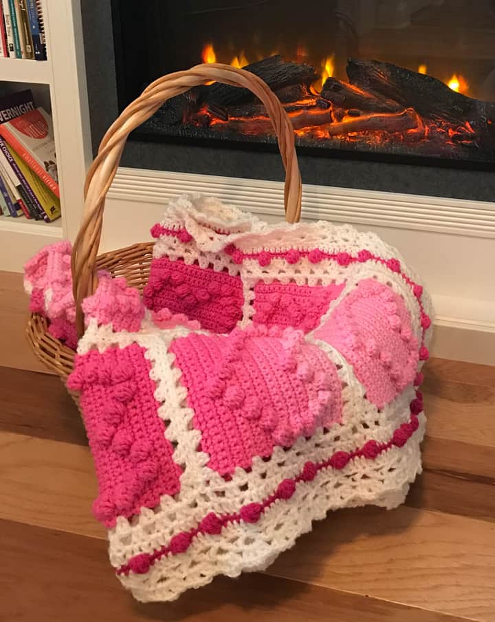 crochet afghan with pink heart squares and a white lacy like border by a fireplace