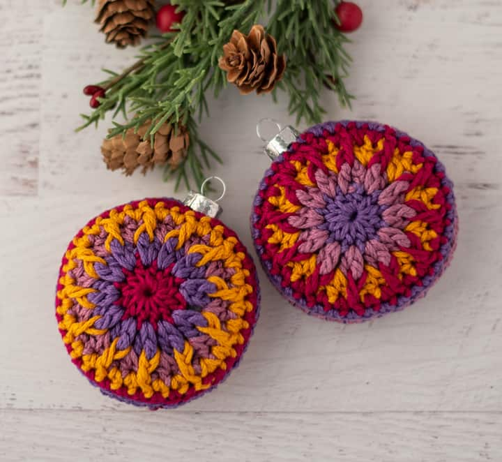 crochet ornaments in jewel tone purple, pink and gold yarn.