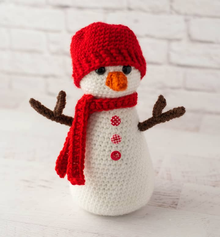 Crochet snowman with red hat and scarf, orange nose and brown twig arms