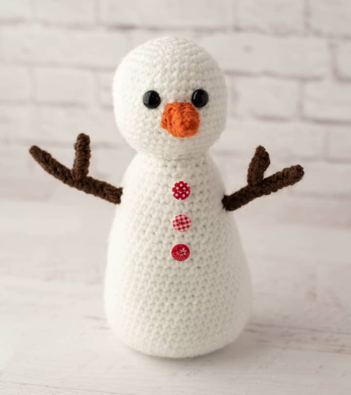 white crochet snowman with brown arms and orange nose