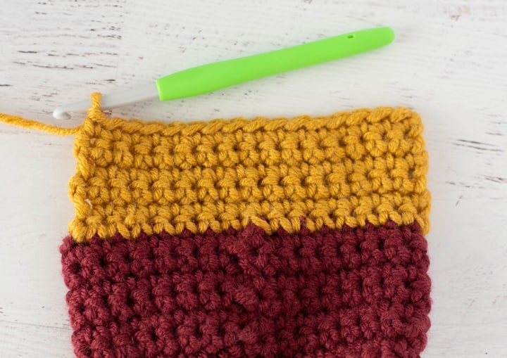 burgundy and yellow crochet stocking heel in progress with green crochet hook