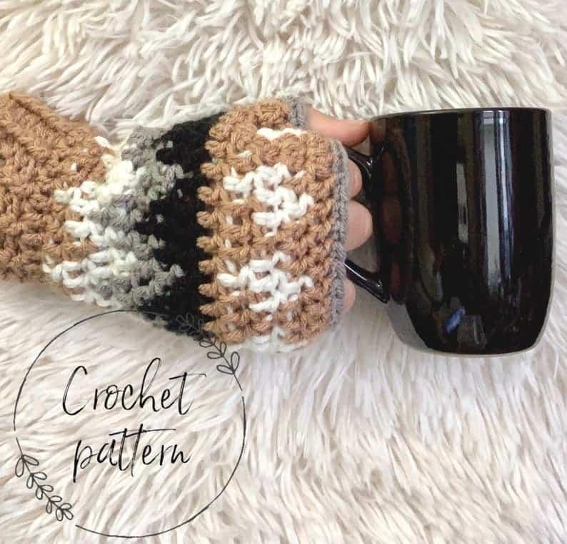 main gantée sans doigts au crochet or, marron et blanc tenant une tasse de café