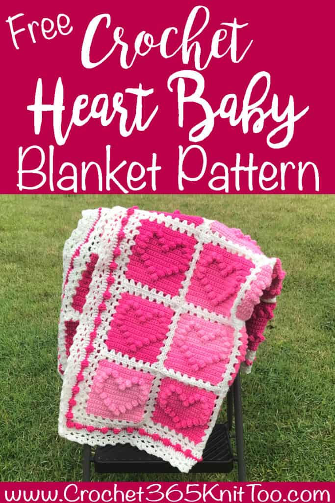 crochet afghan with pink heart squares and a white lacy like border