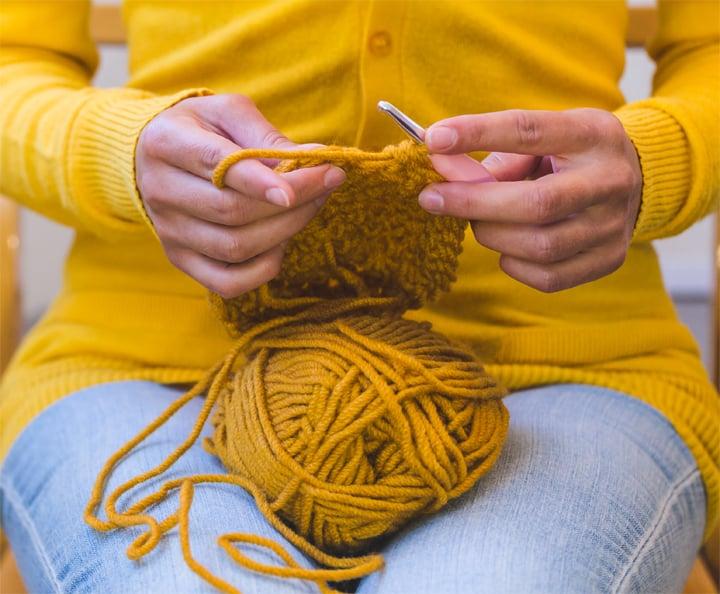 Woman in yellow sweater crocheting with yellow yarn