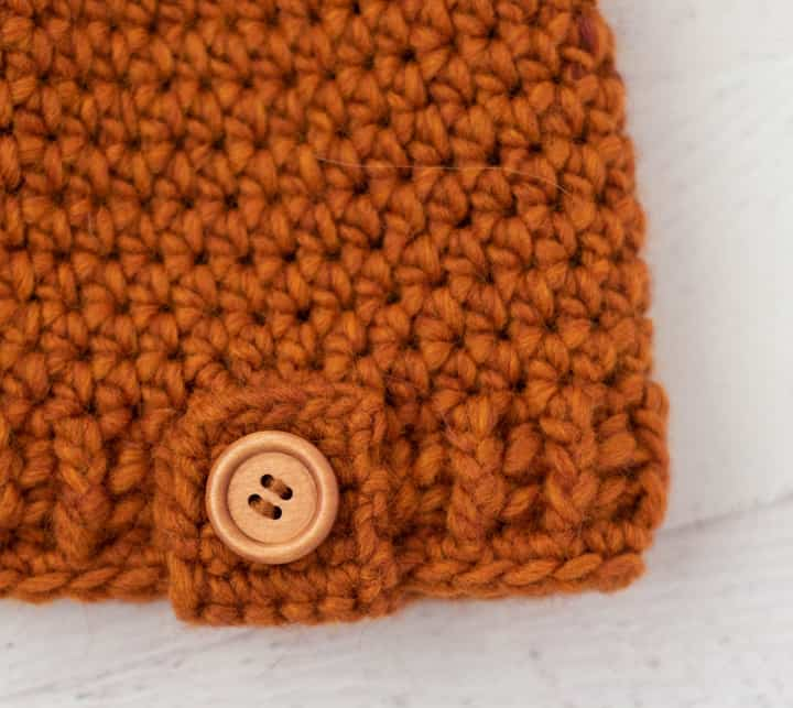 Close up of rust color crochet and wood button