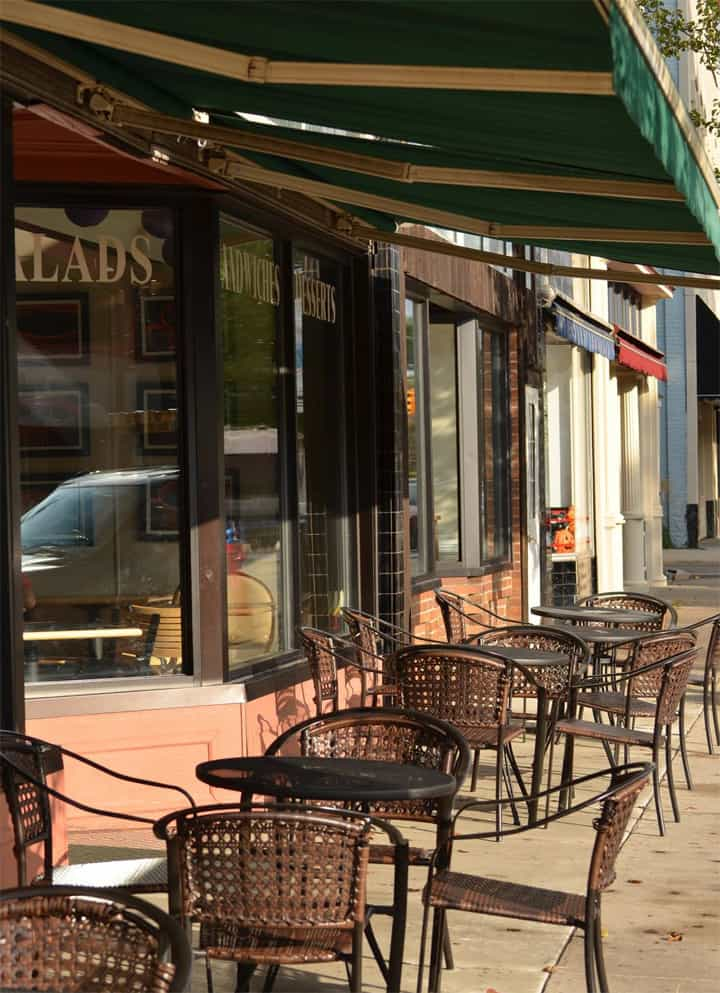 Deli with patio table and chairs on sidewalk
