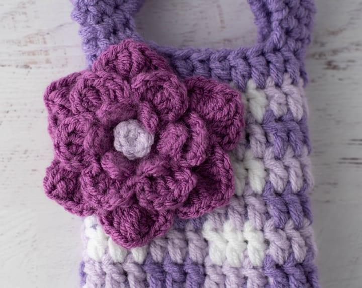 Large purple crochet flower on crochet purple gingham wine cozy