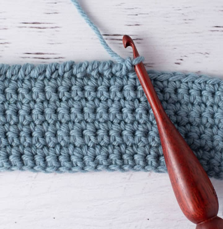 blue crochet piece and wood crochet hook, demonstrating reverse single crochet stitch